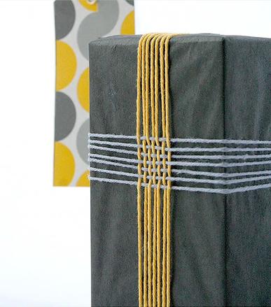 Impacchettare un regalo con spaghi colorati intrecciati
